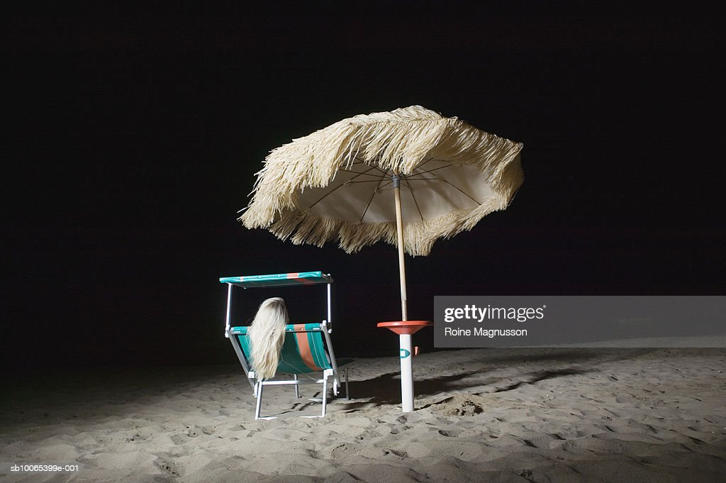 Woman sitting on deck chair on beach at night, rear view : Foto stock