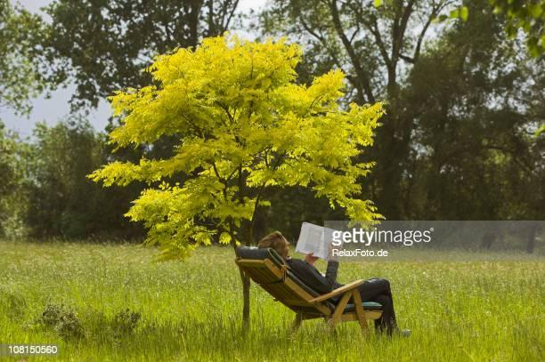 Femme assise sur une chaise en lisant un livre sous arbre (XXL