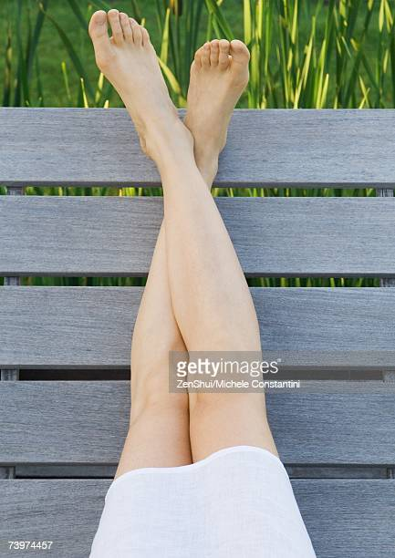 woman sitting on deck, legs crossed at ankles, cropped view of legs - legs crossed at ankle stock pictures, royalty-free photos & images