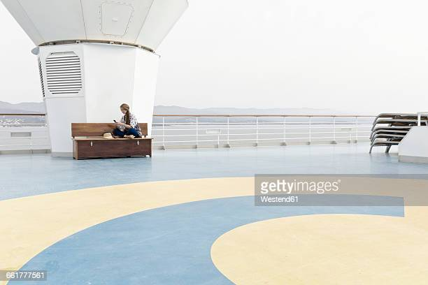 Woman sitting on deck of cruise liner looking at her smartphone