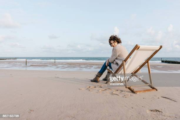 woman sitting on deckchair on the beach - rivage photos et images de collection
