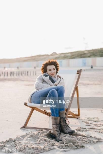 Woman sitting on deckchair on the beach