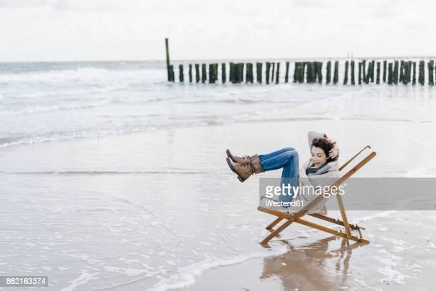 Woman sitting on deckchair on the beach raising her legs