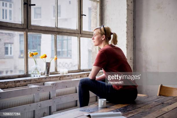 woman sitting on desk in loft looking through window - kaffee oder teepause stock-fotos und bilder