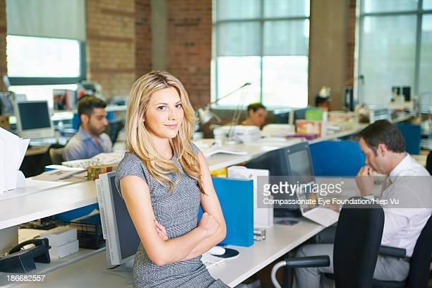 Woman sitting on desk in office