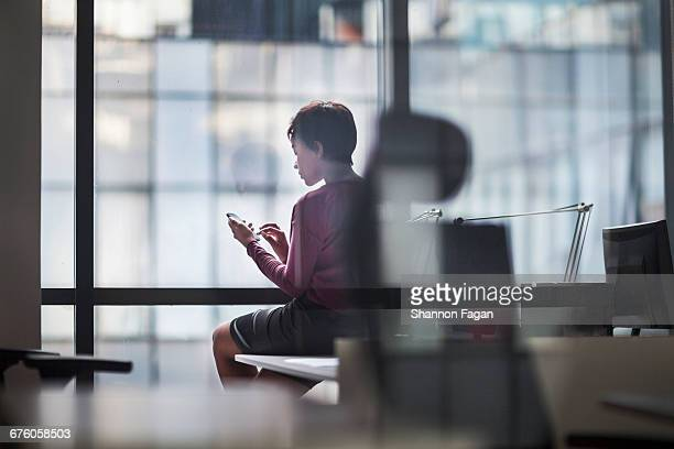 Woman sitting on desk touching smart phone