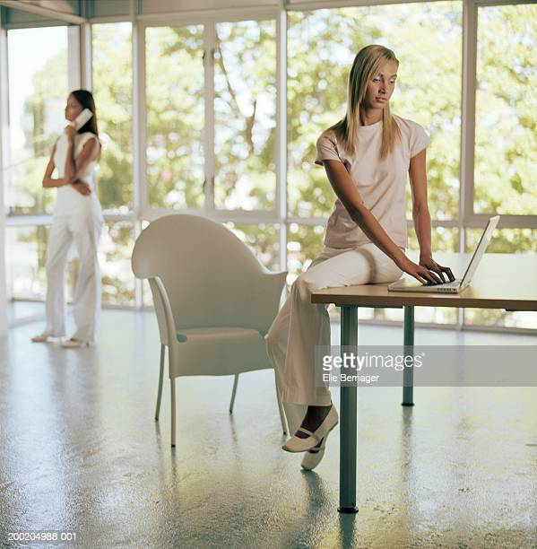 Woman sitting on desk using computer, woman in background using phone