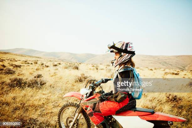 Woman sitting on dirt bike during desert ride
