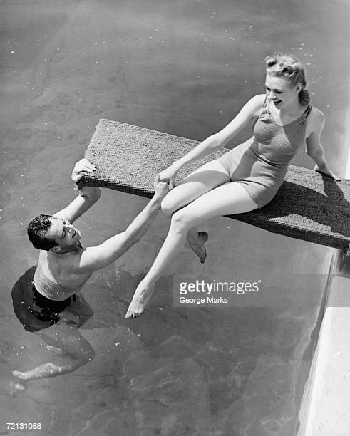 woman sitting on diving board, man grasping her hand (b&w), elevated view - badkleding stockfoto's en -beelden