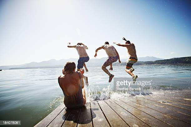 woman sitting on dock while men jump into water - taking the plunge stock photos and pictures