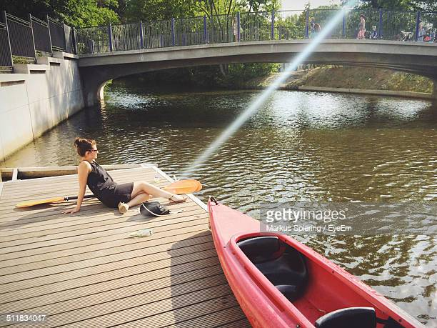 Woman sitting on dock with canoe