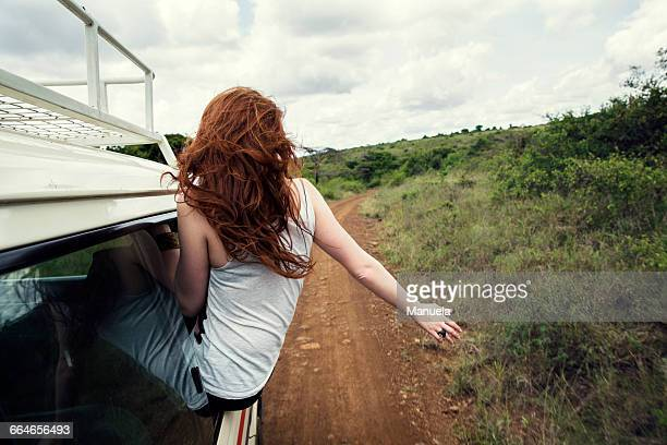 woman sitting on door of vehicle in wildlife park, nairobi, kenya - áfrica del este fotografías e imágenes de stock