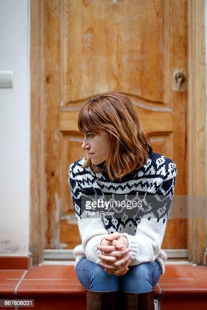 Woman sitting on doorstep looking away