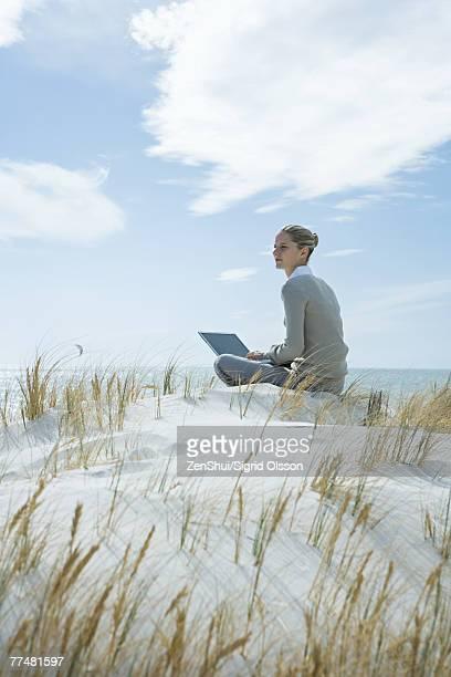 woman sitting on dune, using laptop - blond frauen strand stock-fotos und bilder