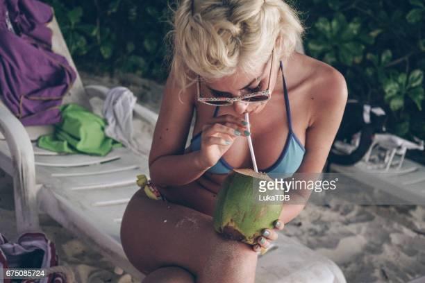 Frau im Sessel sitzen und halten Kokosnuss, Malediven