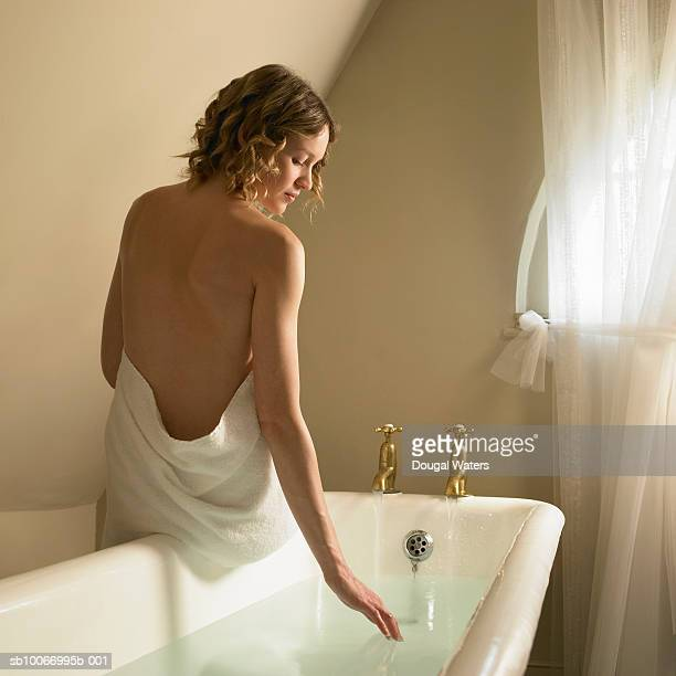 Woman sitting on edge of bath testing water with fingertips, rear view