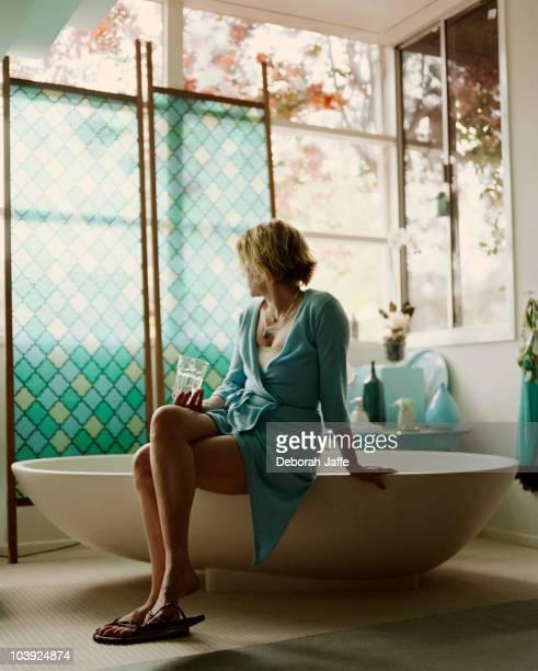 Woman sitting on edge of bathtub