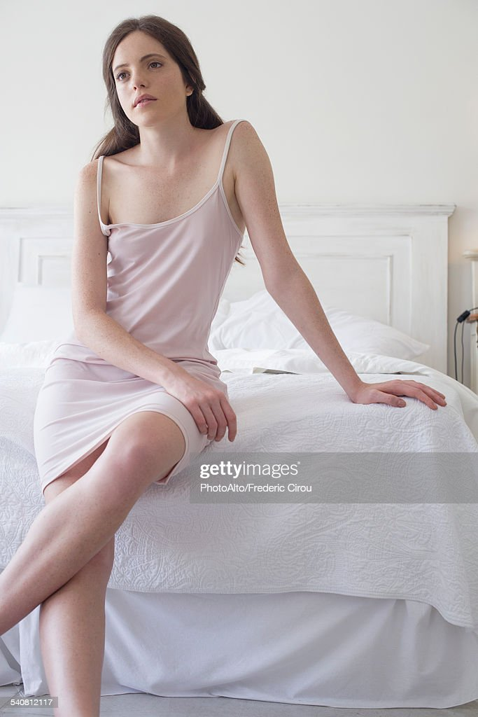 Woman sitting on edge of bed : Stock Photo
