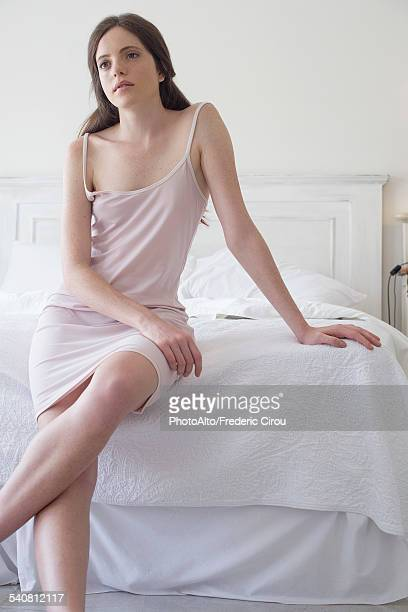 woman sitting on edge of bed - women in slips stock photos and pictures