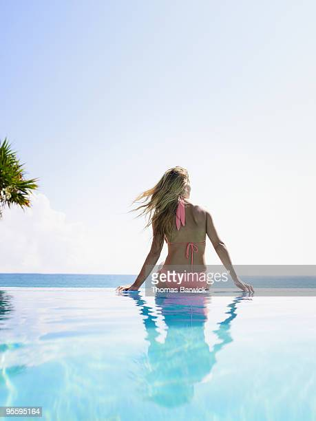 Woman sitting on edge of infinity pool