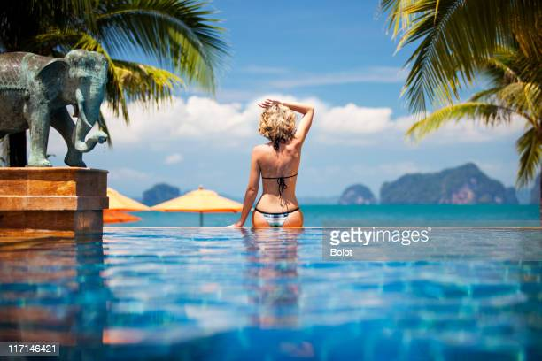 Woman sitting on edge of infinity pool, rear view