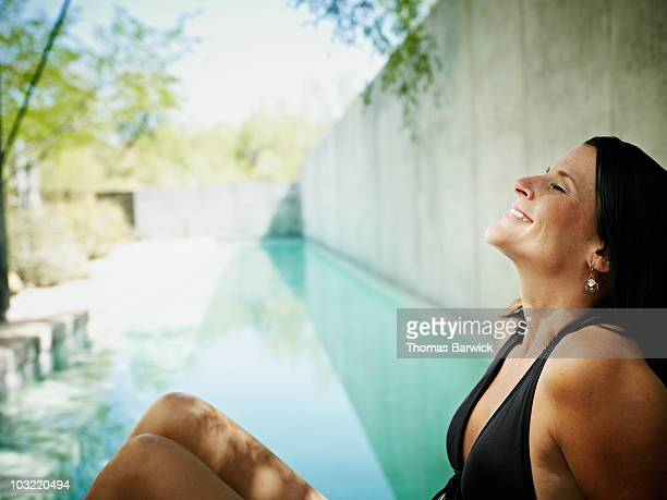 Woman sitting on edge of pool eyes closed smiling