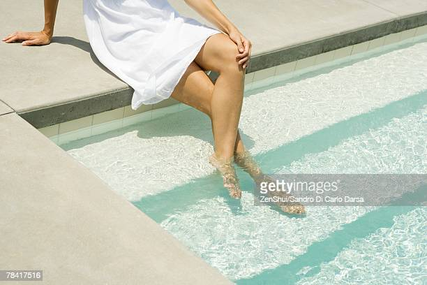 Woman sitting on edge of pool, feet in water, high angle view, cropped