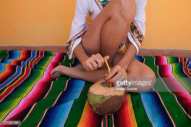Woman sitting on ethnic style blanket with tropical fruit juice