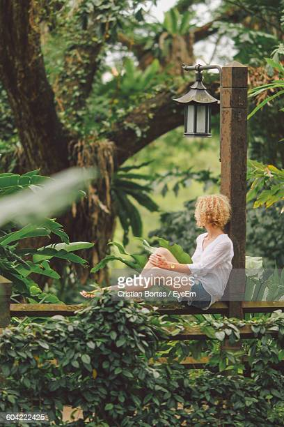 Woman Sitting On Fence Against Trees In Park