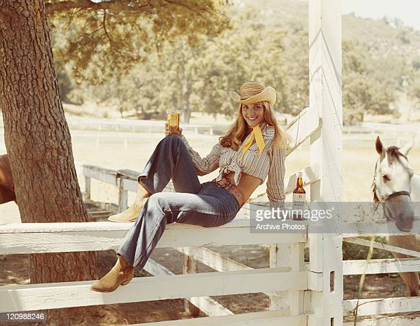 Woman sitting on fence with whisky bottle and glass, smiling portrait