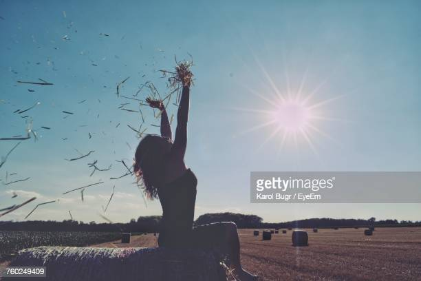 Woman Sitting On Field Against Clear Sky