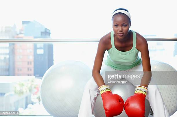 woman sitting on fitness ball wearing boxing gloves - oliver eltinger stock-fotos und bilder