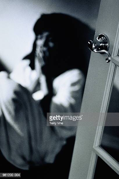 Woman sitting on floor by door, hands to face (B&W)