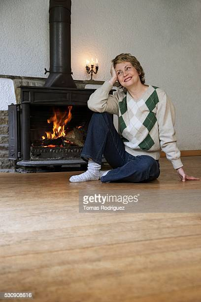 Woman sitting on floor by fireplace