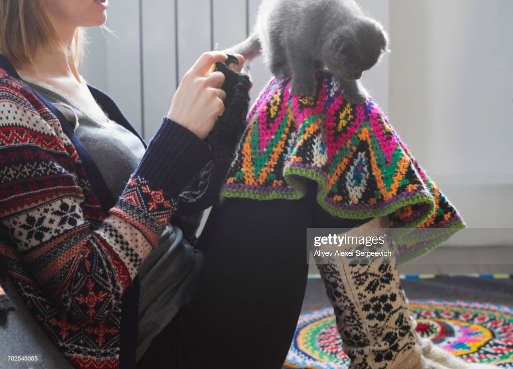 Woman sitting on floor crocheting with kitten balancing on her knee : Stock Photo