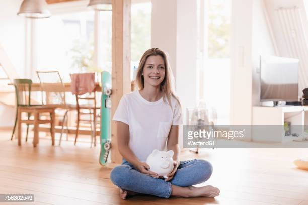 Woman sitting on floor holding piggy bank