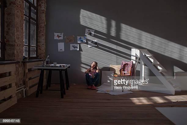 Woman sitting on floor in art studio
