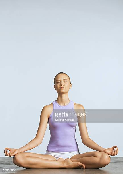 Woman sitting on floor in lotus position