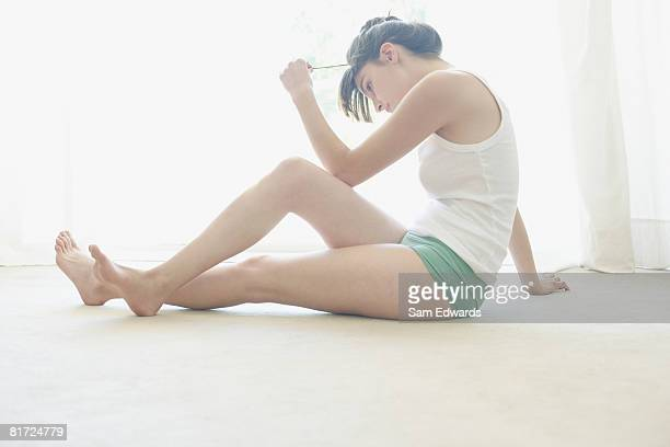 Woman sitting on floor indoors playing with hair