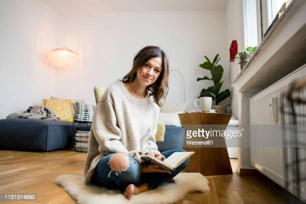 woman sitting on floor, journalising in her diary - tagebuch stock-fotos und bilder