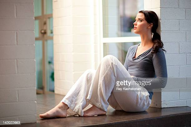 Woman sitting on floor leaning on wall