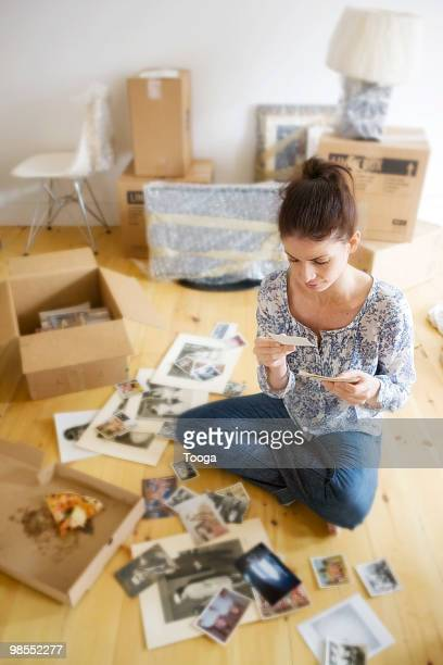 Woman sitting on floor looking at family pictures