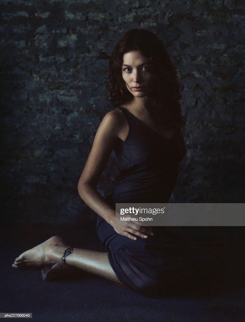 Woman sitting on floor, looking into camera, portrait. : Stockfoto