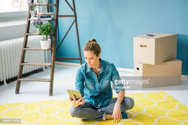 Woman sitting on floor of her new apartment, using digital tablet