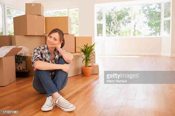 Mulher sentada no chão da nova casa