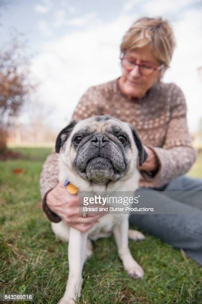 Woman Sitting on Grass holding her Pug Dog