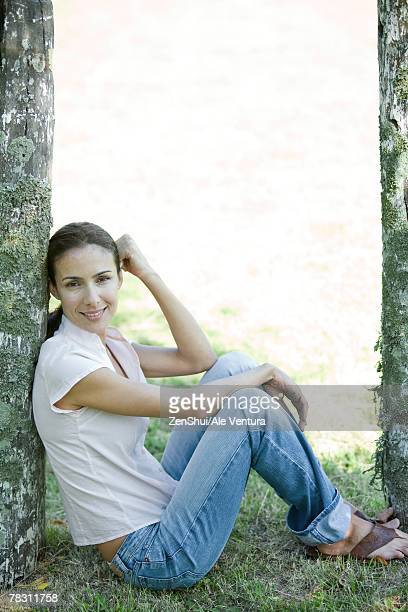Woman sitting on grass, leaning against wooden post, full length