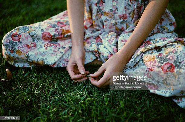 woman sitting on grass - floral pattern dress stock pictures, royalty-free photos & images