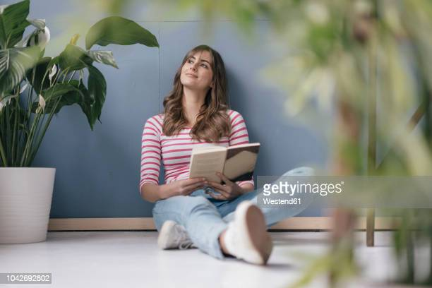 woman sitting on ground in her new home, reading a book, surrounded by plants - tagträumen stock-fotos und bilder