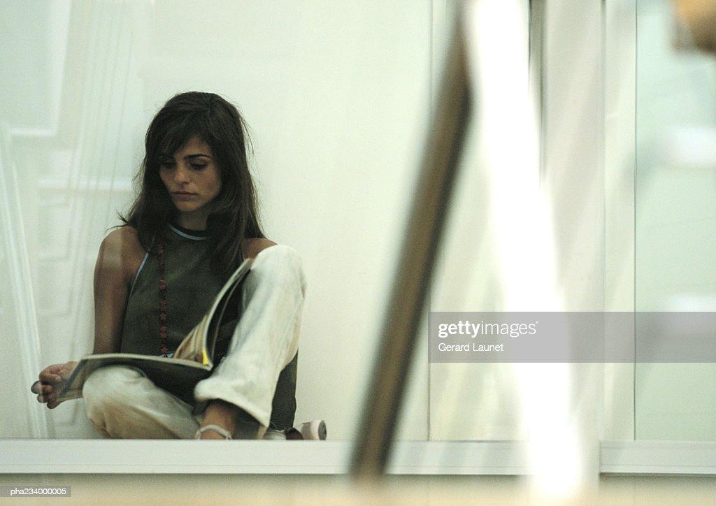 Woman sitting on ground, legs crossed, reading. : Stockfoto